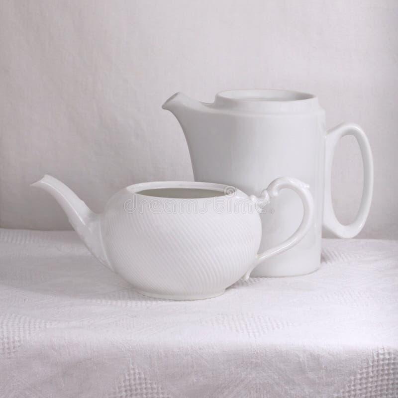White porcelain pots. Two white porcelain pots on a white tablecloth stock images