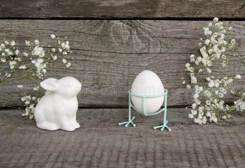 White porcelain rabbit and white chiken eggs on vintage wooden background. Easter`s Background. Retro style. royalty free stock photos