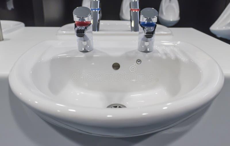 White porcelain sink. In a public bathroom stock photos