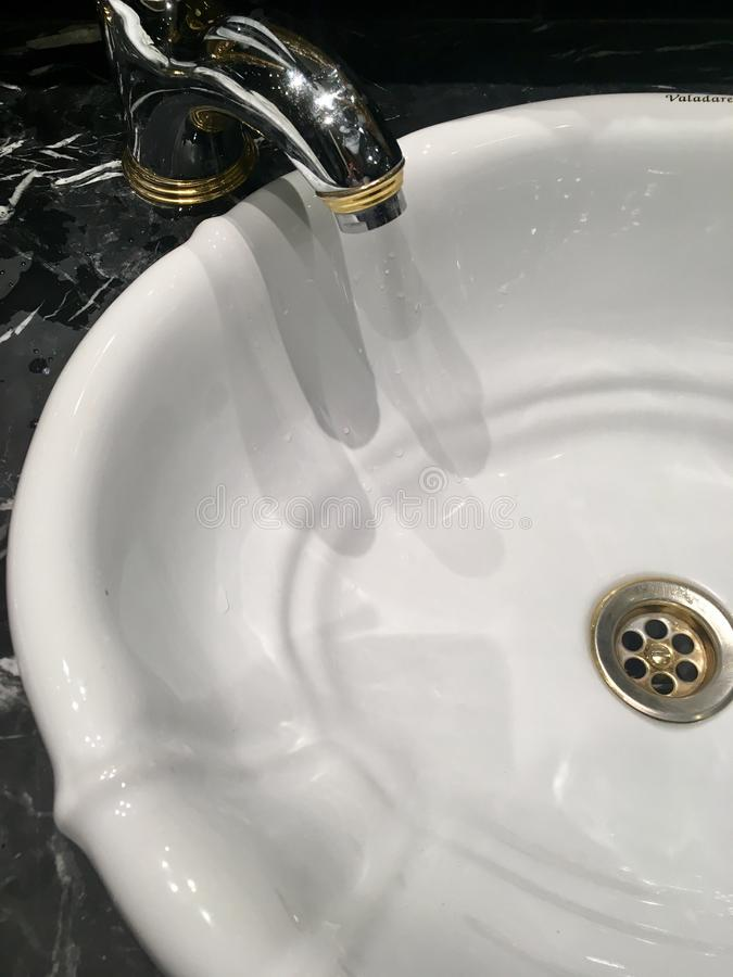 White Porcelain Sink. A white porcelain sink is surrounded by striking black marble stock photos
