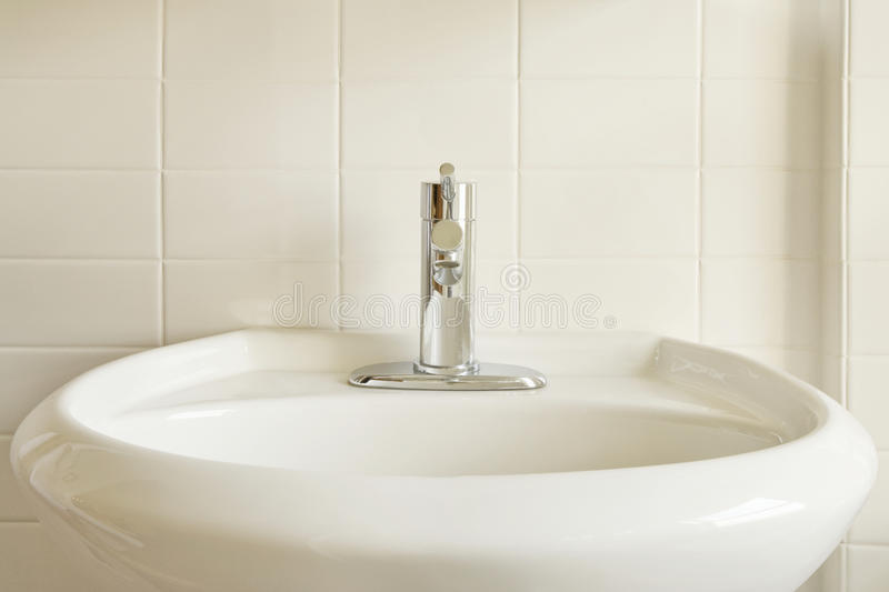 White Porcelain Sink and White Tile. Close-up of a modern stainless steel faucet on an oval, white porcelain pedestal-style sink against a white tile wall stock photos
