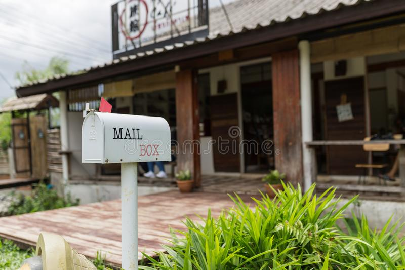A white post box with a red flag, Mailbox. Letterbox royalty free stock images