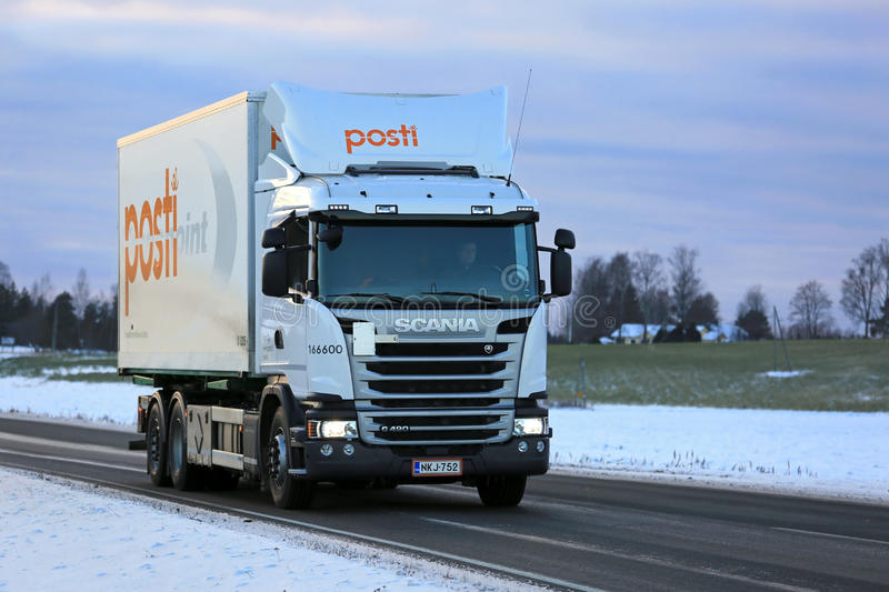 White Posti Group Delivery Truck on the Road in Evening. SALO, FINLAND - NOVEMBER 11, 2016: Scania G490 delivery truck of Posti Group, Finnish Post moves along stock photo