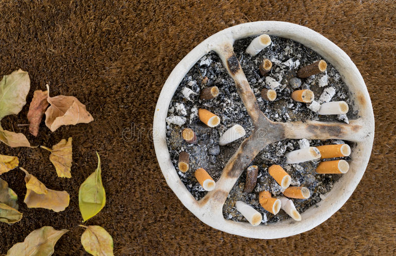 White pottery ashtray with cigarettes and ashes and dead leaves. White pottery handmade ashtray full of a huge number of cigarettes and ashes on a background of royalty free stock photography