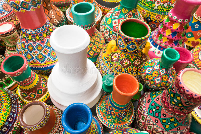 White pottery vase surrounded with collection of painted colorful vases. Angled view showing a composition of artistic painted handcrafted colorful pottery vases royalty free stock photo