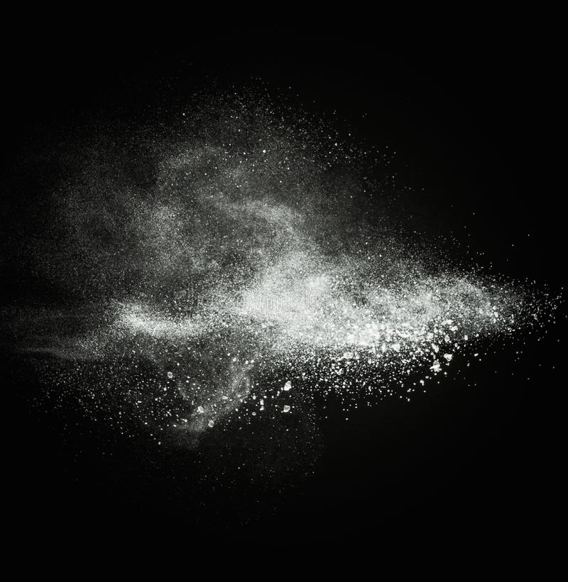 White powder exploding. Isolated on black stock image