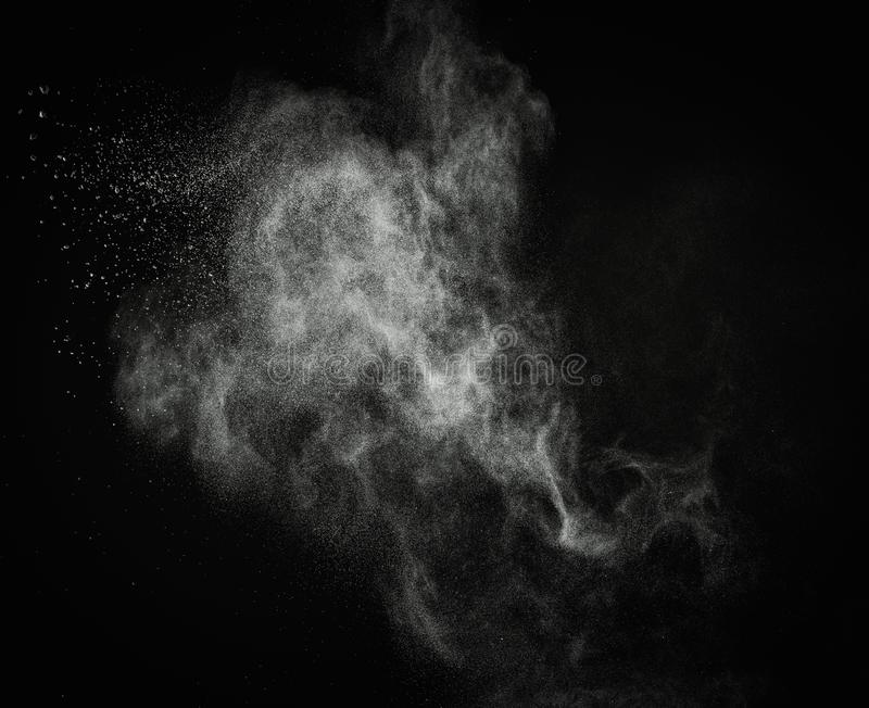 White powder explosion. White powder exploding isolated on black stock photography