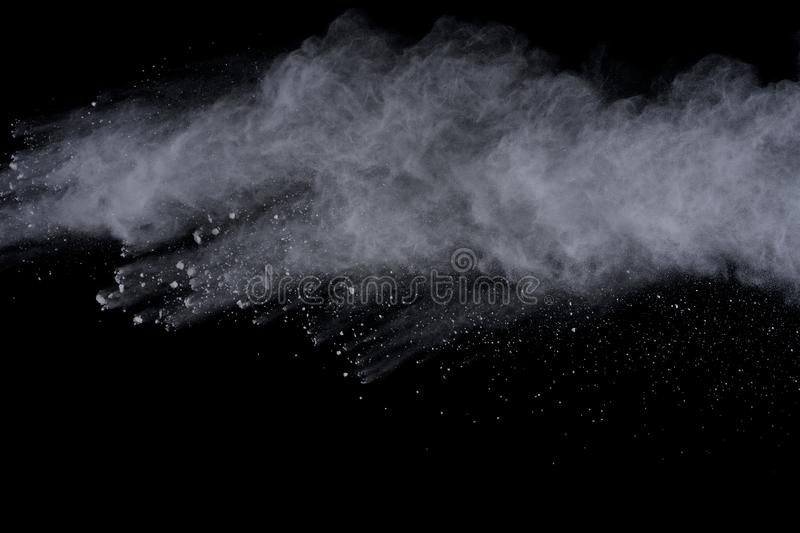 White powder explosion isolated on black background. Colored dust splatted. stock photo