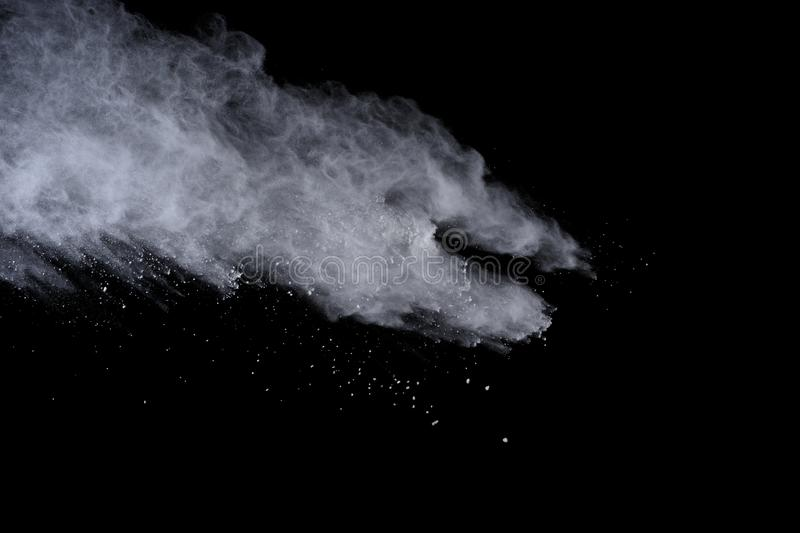 White powder explosion isolated on black background. Colored dust splatted. stock photos