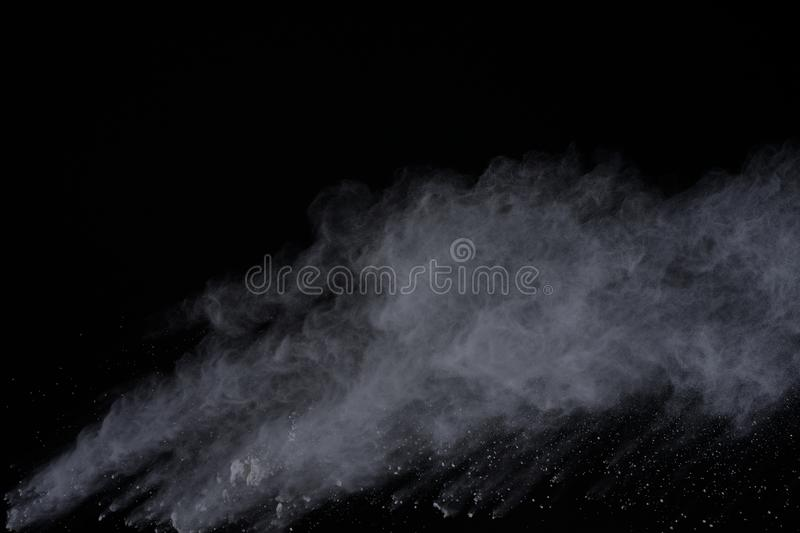 White powder explosion isolated on black background. Colored dust splatted. royalty free stock photo