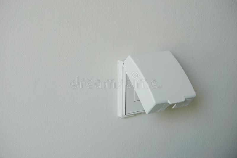 White power outlet cover, plug housing or plug socket. With waterproof cover on white wall .Electric safety concept royalty free stock image