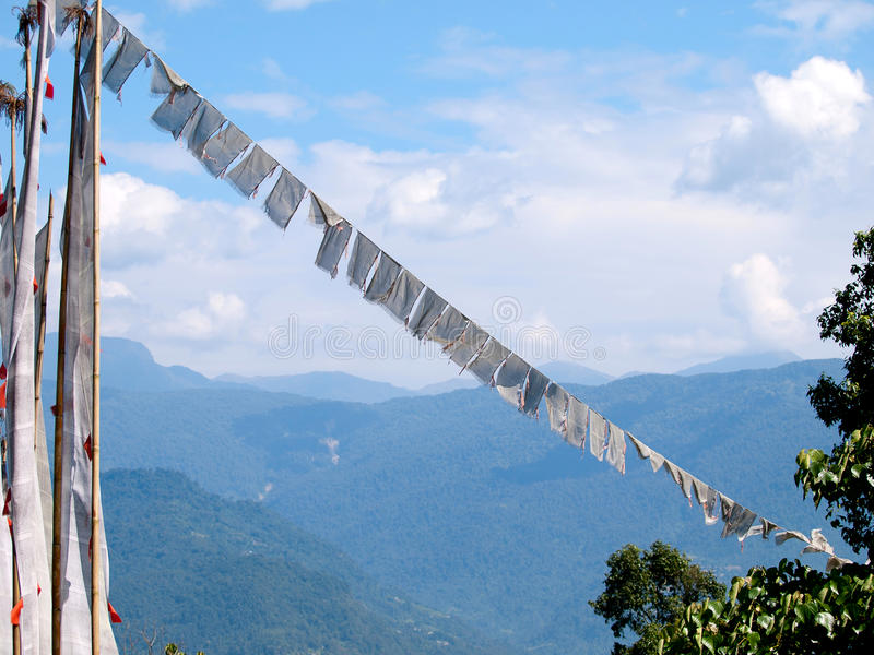 White prayer flags over a clear blue sky in India royalty free stock images