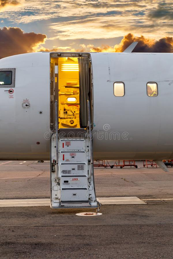 White private jet and open ladder at the airport against the background of dramatic sky and sunset royalty free stock images