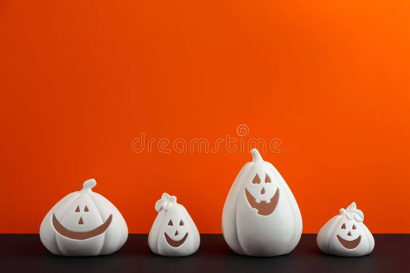White pumpkin shaped candle holders on black against orange background, space for text. Halloween decoration. White pumpkin shaped candle holders on black table royalty free stock photo