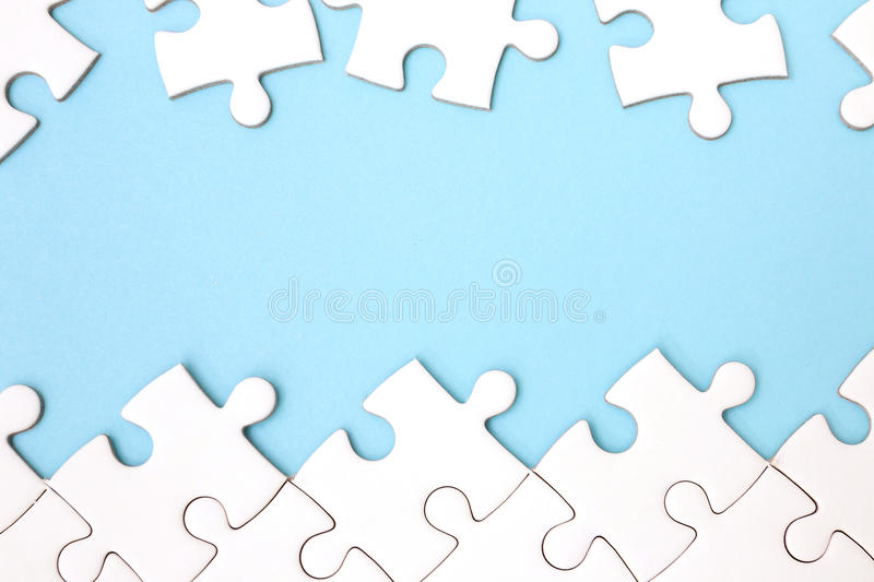 White puzzle frame on pastel blue background. With copy space royalty free stock image