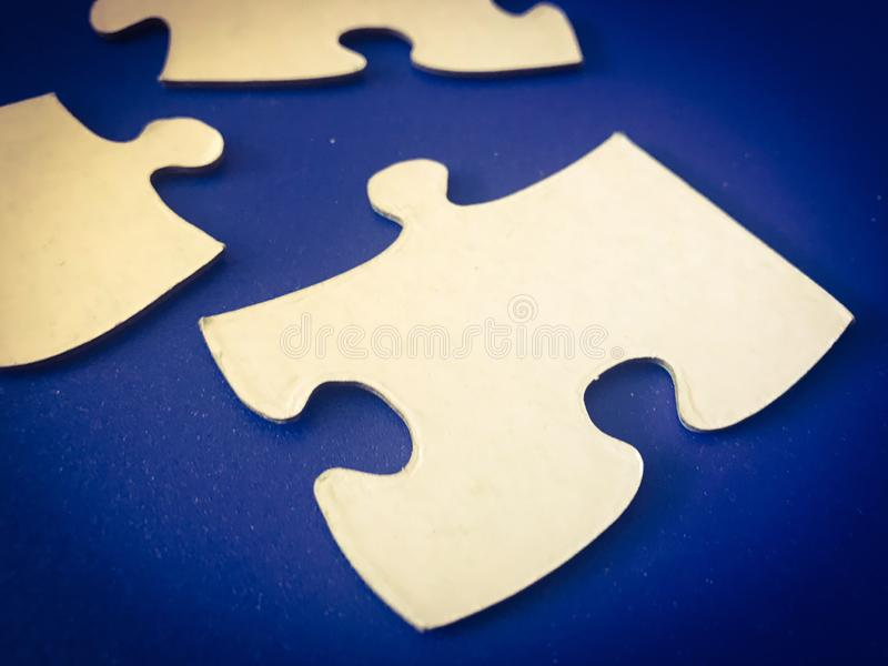 White puzzle pieces in a blue background stock photography