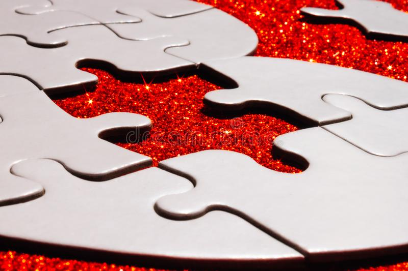 White puzzle on red sparkle background. White heart shaped puzzle with missing part on red sparkle background stock image
