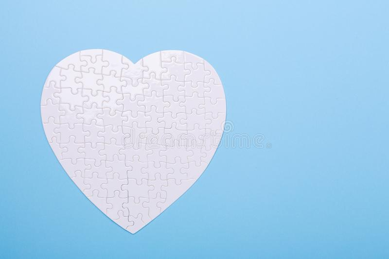 White puzzle in shape of heart on blue background Jigsaw Concept treatment of heart disease pills royalty free stock photos