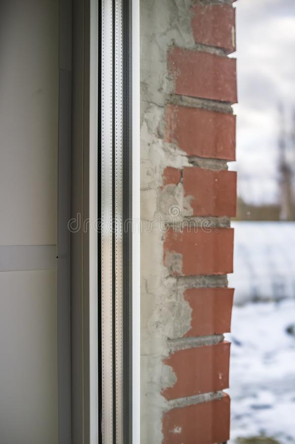 White PVC window with double glazing in a brick house. Close-up royalty free stock photo