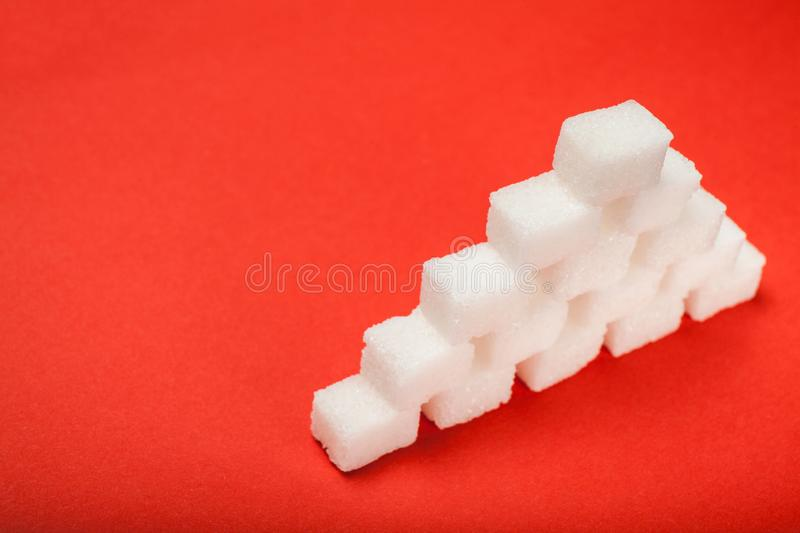 White pyramid of cubes of sugar on a red background. Unhealthy eating royalty free stock image