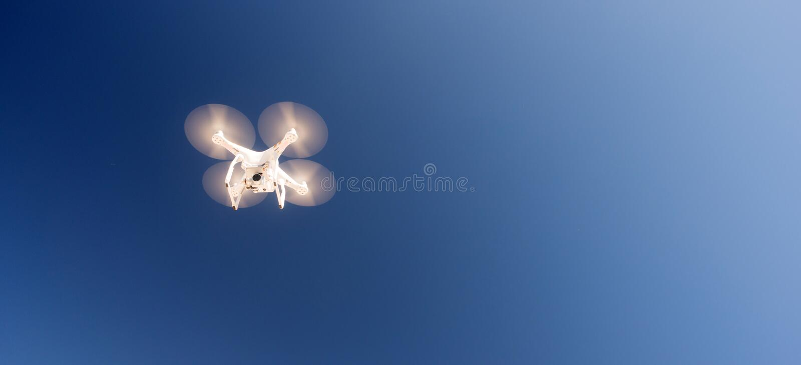 White Quadcopter Drone Flying Hoovering Blue Sky royalty free stock images