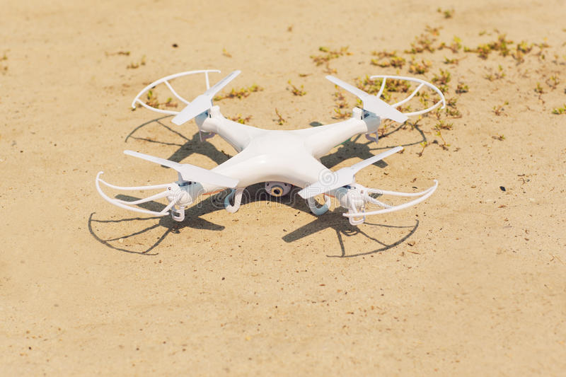 White quadrocopter on sand, close-up. New unmanned aerial copter in dessert. Electronics innovation. Modern Technologies. Aeromodelling royalty free stock images