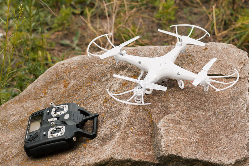 White quadrocopter on stone, close-up. White quadrocopter on stone with remote control, close-up. New unmanned aerial copter. Electronics innovation. Modern royalty free stock photography