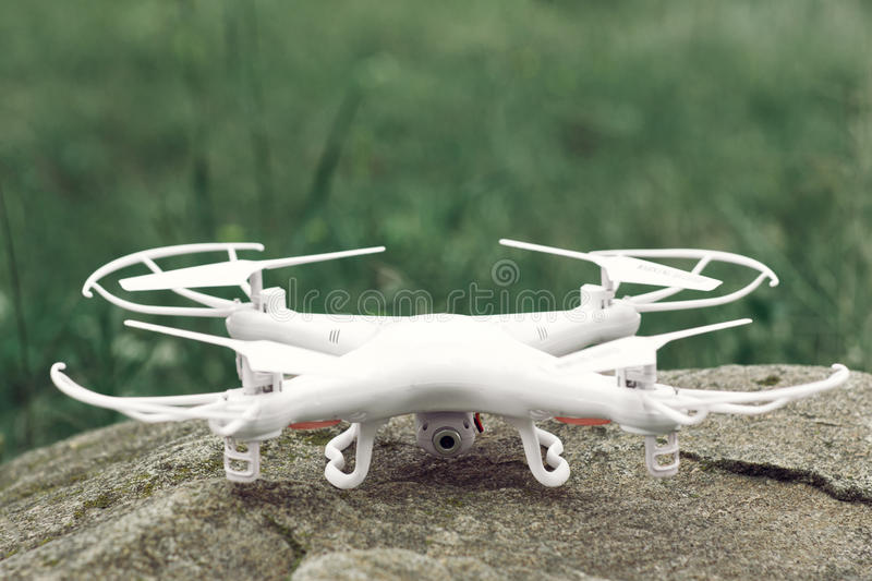 White quadrocopter on stone, drone, close-up. New unmanned aerial copter. Electronics innovation. Modern Technologies. Aeromodelling. New tool for overhead stock image