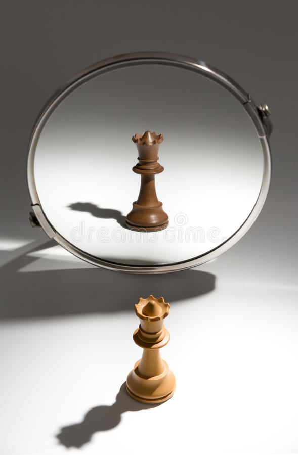 A white queen is looking in a mirror to see herself as a black queen. stock image