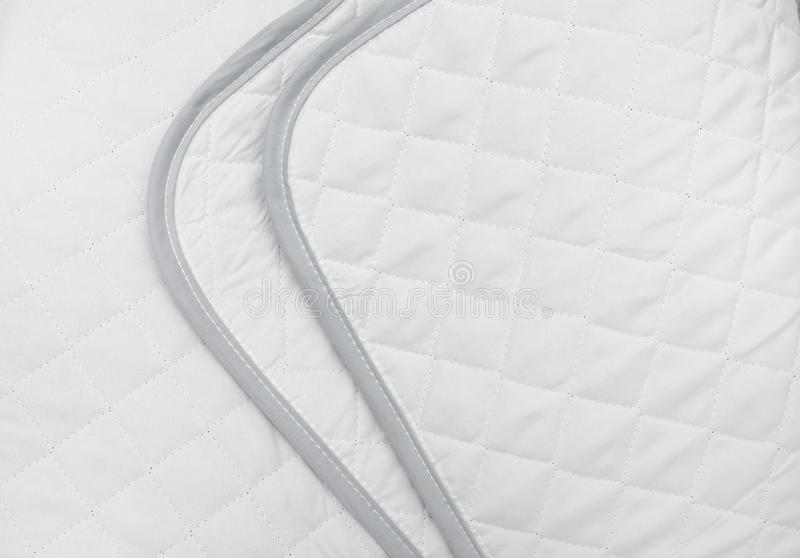 White quilted fabric. The texture of a blanket or bedspread royalty free stock image