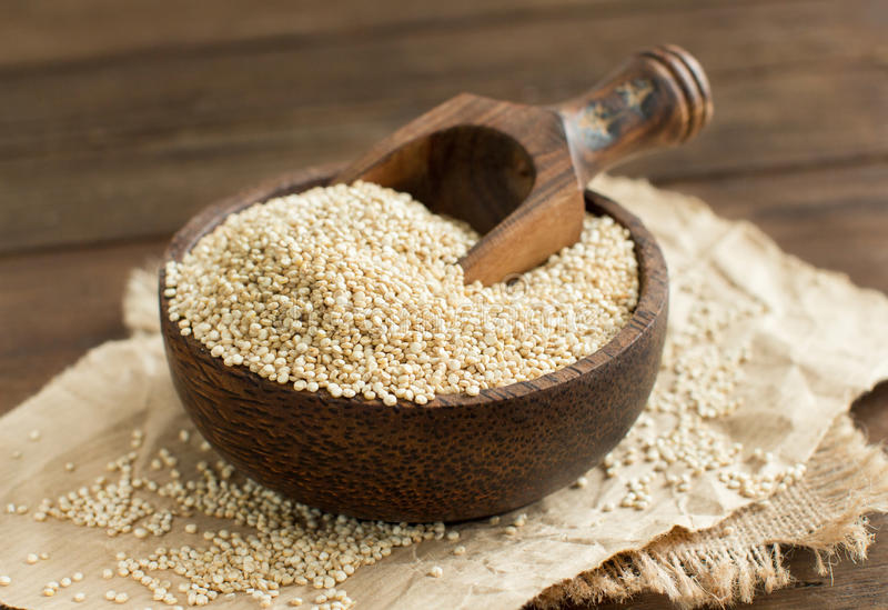 White Quinoa in a bowl with a wooden spoon. Close up royalty free stock photography
