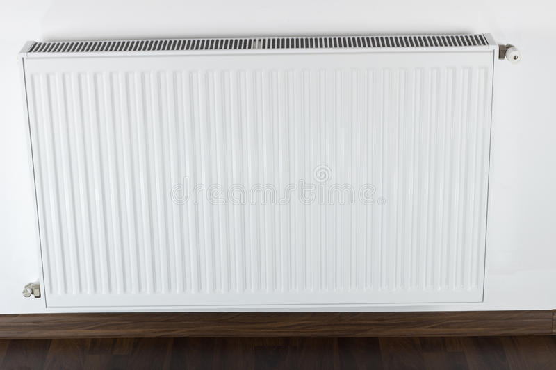 White radiator. White home radiator on a wall stock image