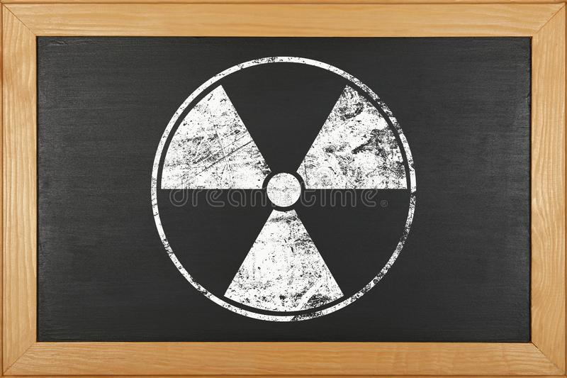 White radioactive sign over black background. White chalk radioactive hazard warning sign over grunge black background of chalkboard with copy space royalty free stock image