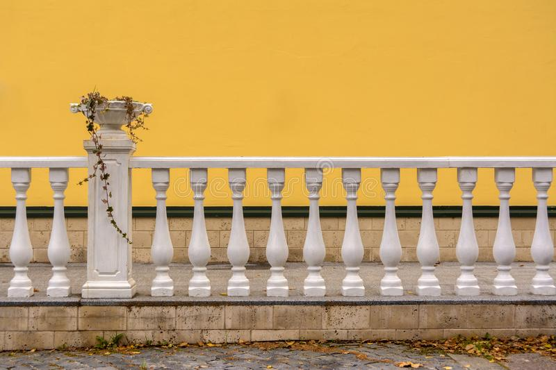 White Railing with columns and a vase for flowers. The wall is painted with yellow paint. Railing with columns and a vase for flowers. The wall is painted with stock photography