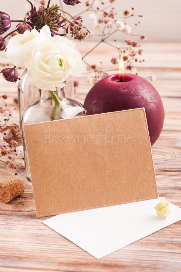 White ranunculus and hydrangea flowers. In bottle with craft envelope on pink rustic wooden background stock image