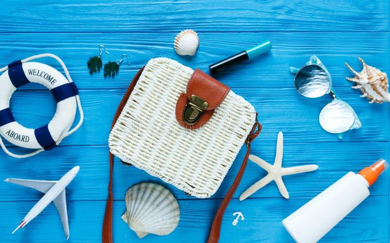 White rattan bag on blue background. Bamboo trendy bag, starfish, shells. Summer fashion flat lay, tourism, vacation, travel stock photos