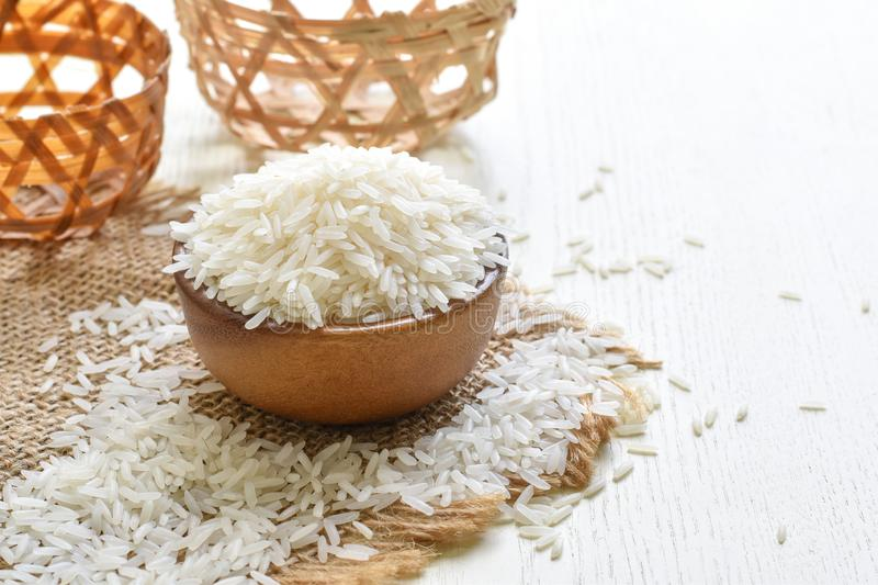White raw rice in a wooden cup for cooking stock photo