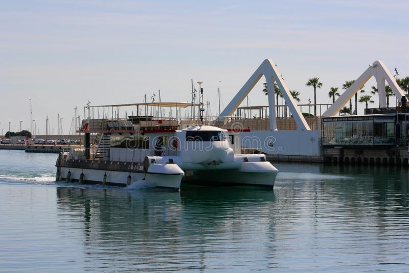 White recreational catamaran returns to the port of Valencia, Spain royalty free stock image