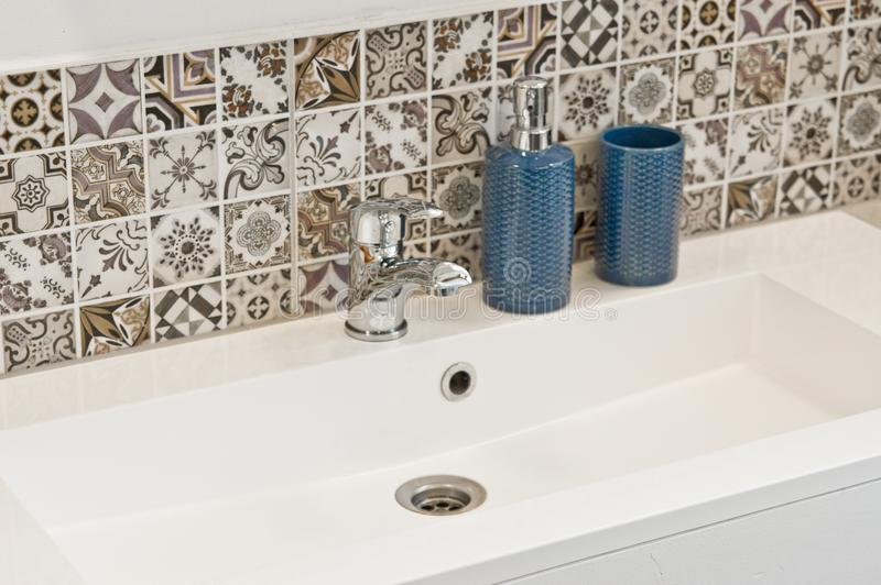White rectangular sink detail with chrome tap royalty free stock image