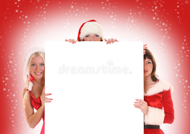 White and red. Three beautiful Santa-girls holding white banner stock photography