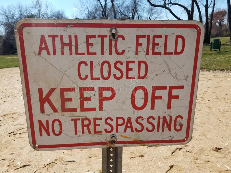 White and red athletic field closed keep off no trespassing sign on dirt royalty free stock photos