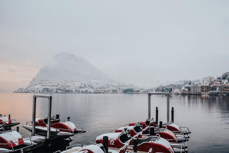 White and Red Boats on Dock Near White Snowy Mountain stock photography