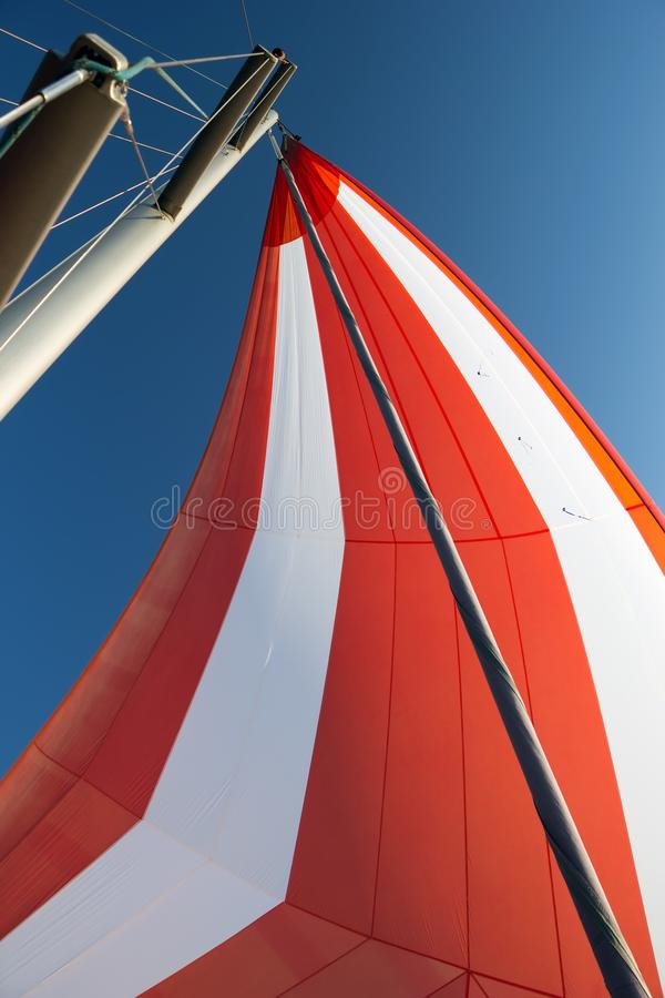 White-red developing sail on a yacht mast against the blue sky, bottom view. Traveling by sea on sunny day. Leisure. Activities at sea. Competitions on yachts royalty free stock images