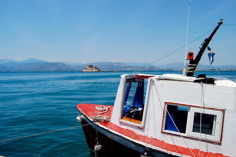 White and Red Fishing Boat. Greek islands are populated with fishing boats in every little seaside port. This one with the bright red decking was tied up to royalty free stock photos