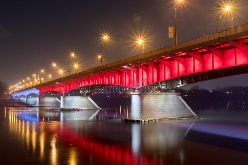 White and red illuminated at Slasko-Dabrowski bridge over Vistula River at night in Warsaw, Poland royalty free stock image