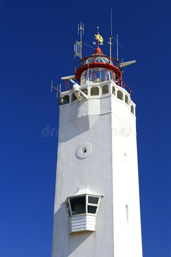 White and red lighthouse on the dutch. Coast in Noordwijk stock images