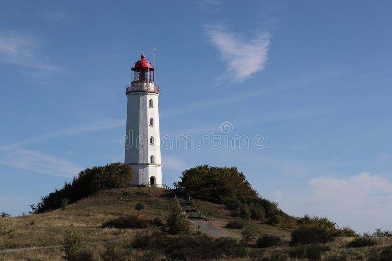 White and red lighthouse on a hill with blue sky and cirrus clouds royalty free stock images