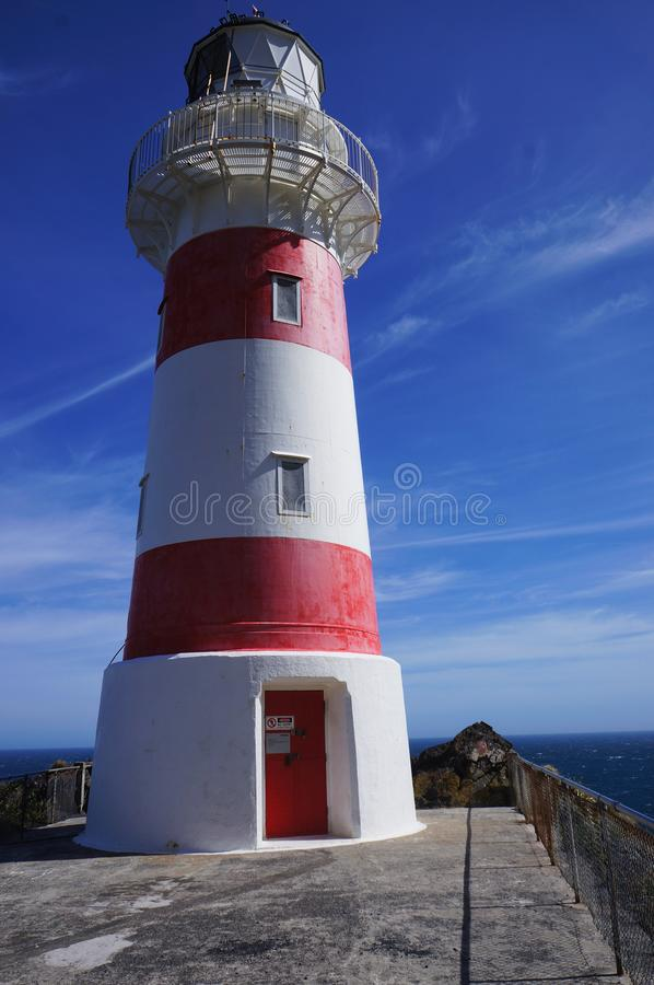 White and red lighthouse. White and red colored lighthouse on the shore royalty free stock photo