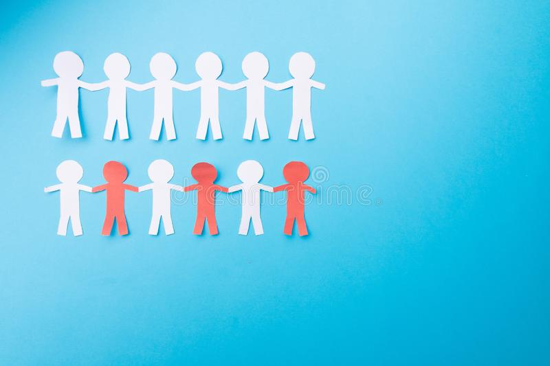 White and red paper people holding hands. Blue background. Froma bove. White and red paper people holding hands. Blue background, community, chain, social, group stock images