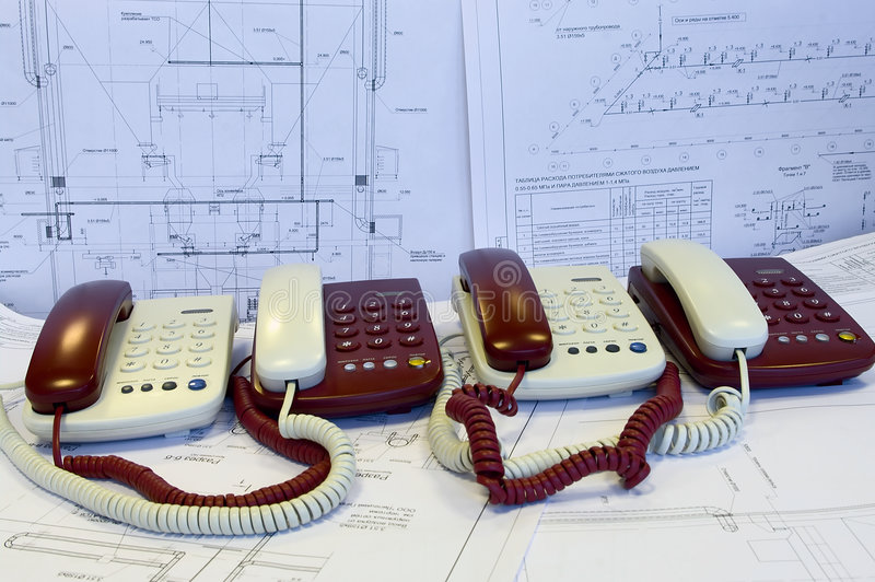 White and red phones are on the working drawings royalty free stock photography